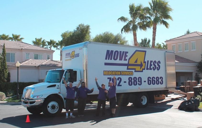 four move 4 less movers in front of moving truck waving to camera