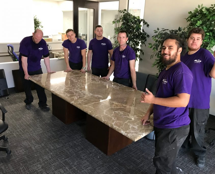 Move 4 Less team of commercial move specialists place a marble conference table