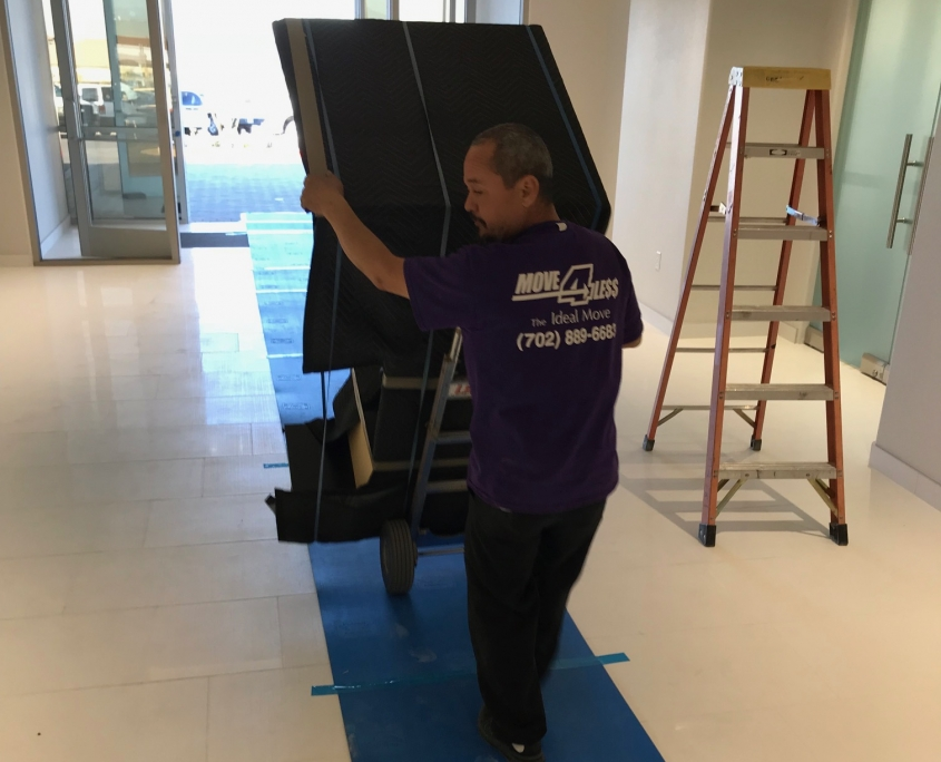 Commercial Mover handling dolly on blue carpet during an office move