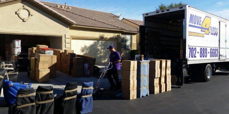 Move 4 Less mover in driveway of home with boxes and moving truck