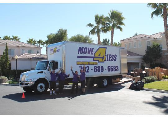 Four members of Move 4 Less team Las Vegas waving to the camera in front of their moving truck