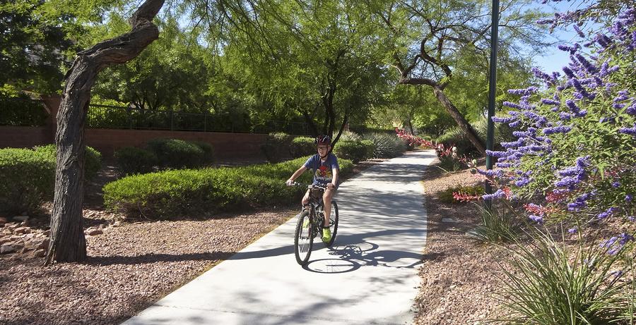 A boy rides a bike on a Summerlin neighborhood bike trail in Las Vegas