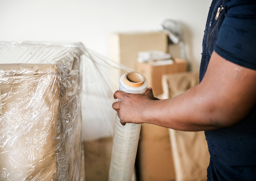 Man putting bubble wrap on furniture for a move