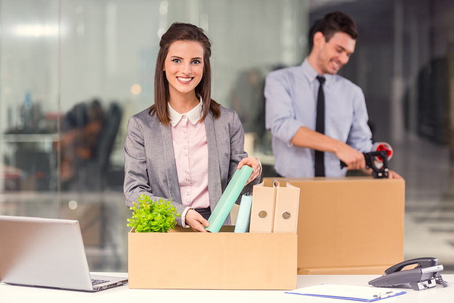 Young happy businessman and a business woman with boxes for moving into a new office