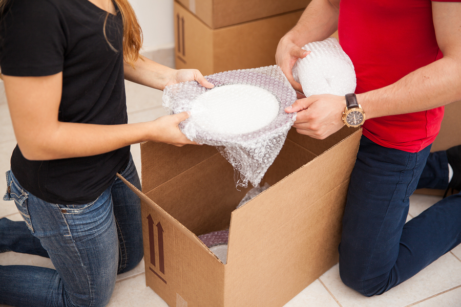Closeup of a young couple using bubble wrap to pack dishes in boxes before moving out