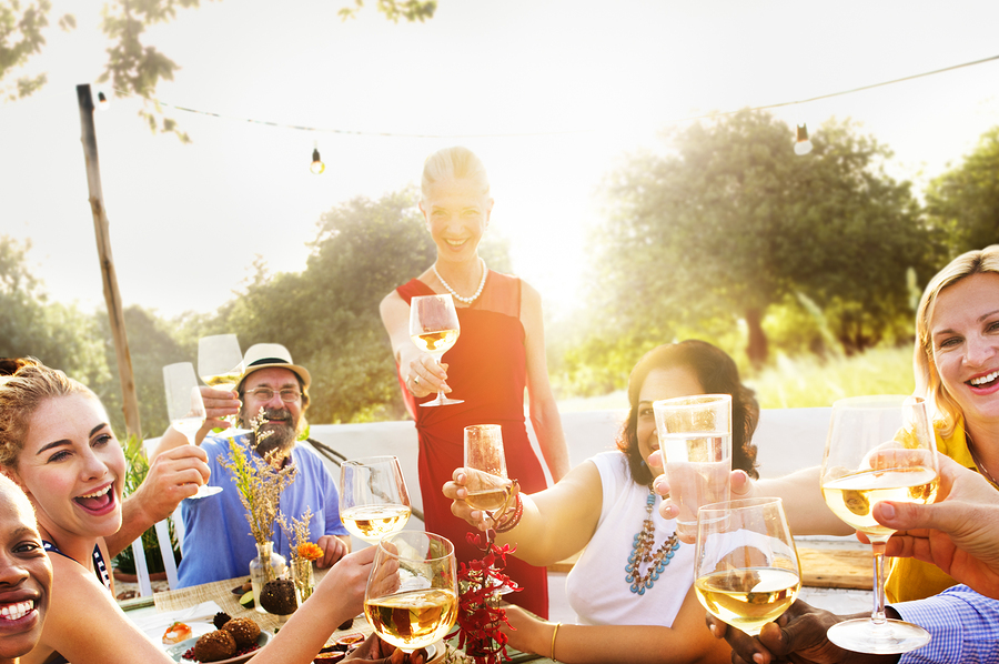 Several neigbors with champagne at picnic table at neighborhood gathering