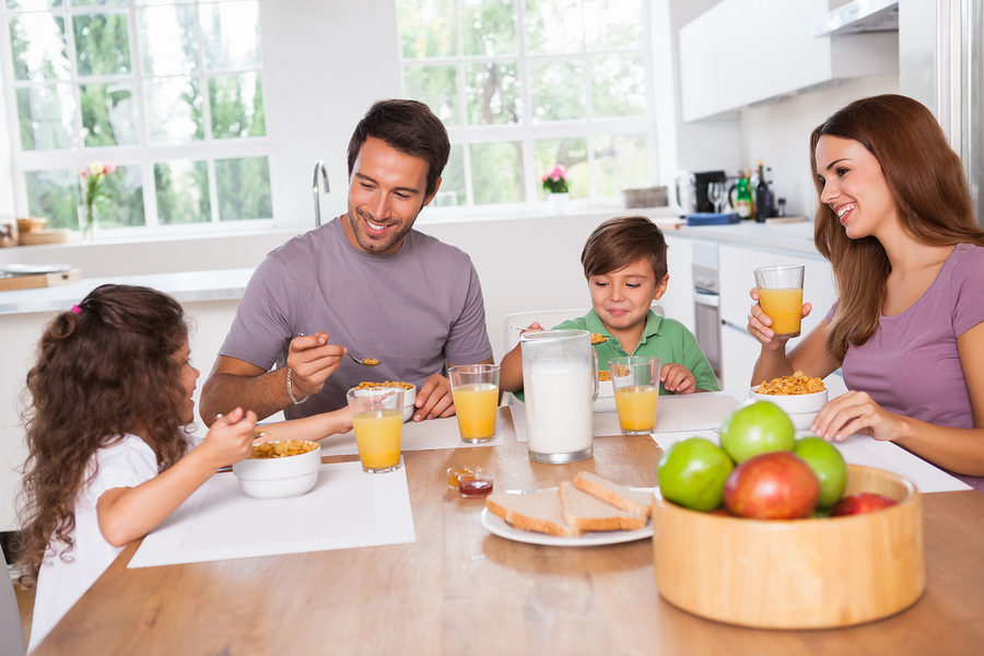 Family eating healthy breakfast in kitchen before school day