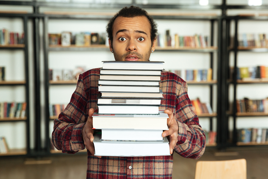 man with a pile of old books off his bookshelf