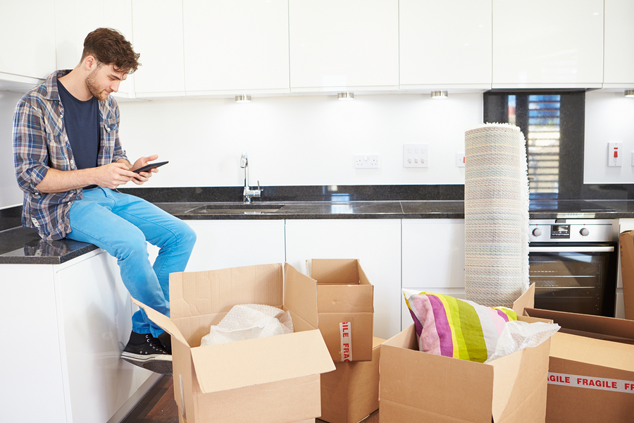 Man Sending Text Message Having Moved Into New Home