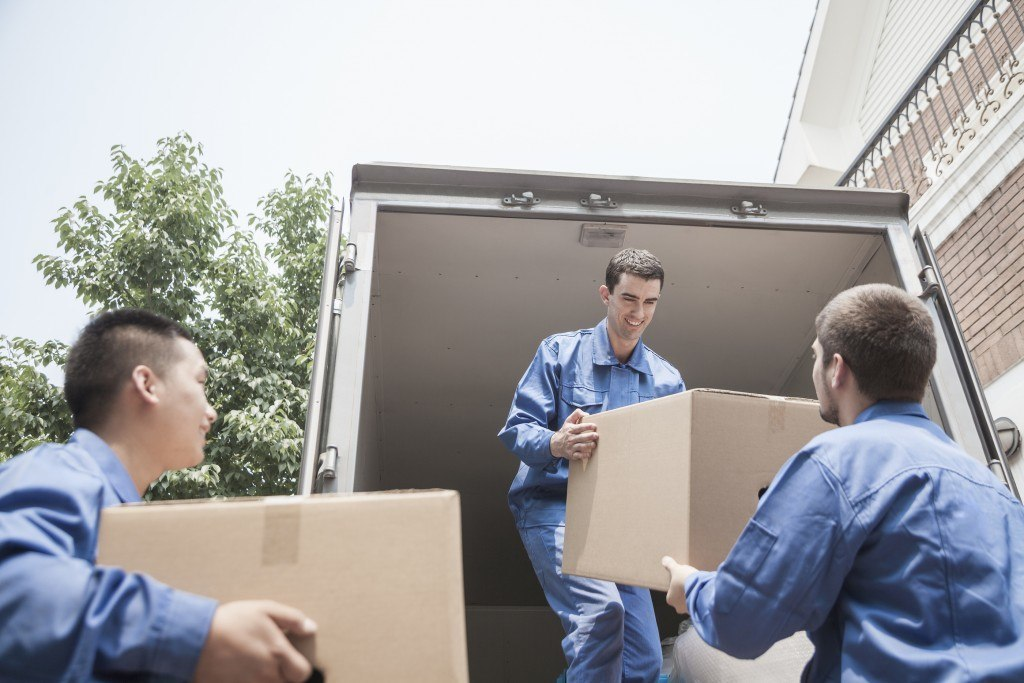 Movers helping to unload boxes from a moving truck