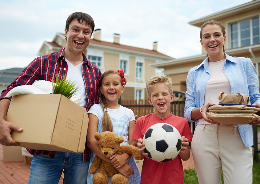 happy family of four outside their home with items showing they are ready to move to a new home