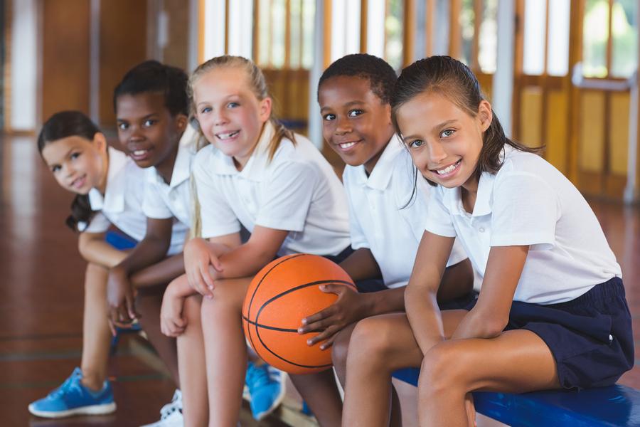 Portrait of school kids sitting in basketball court at school