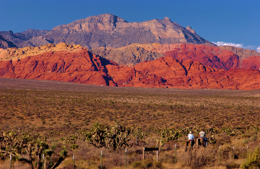two cowboys riding into the sunset. red rock canyon las vegas nevada