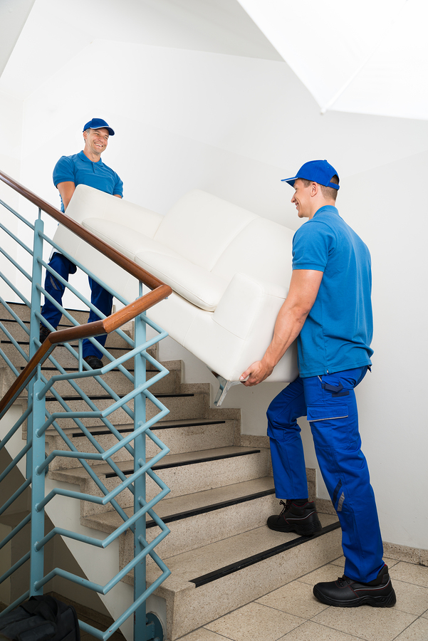 Two Happy Male Movers In Uniform Carrying White Sofa On high rise Staircase