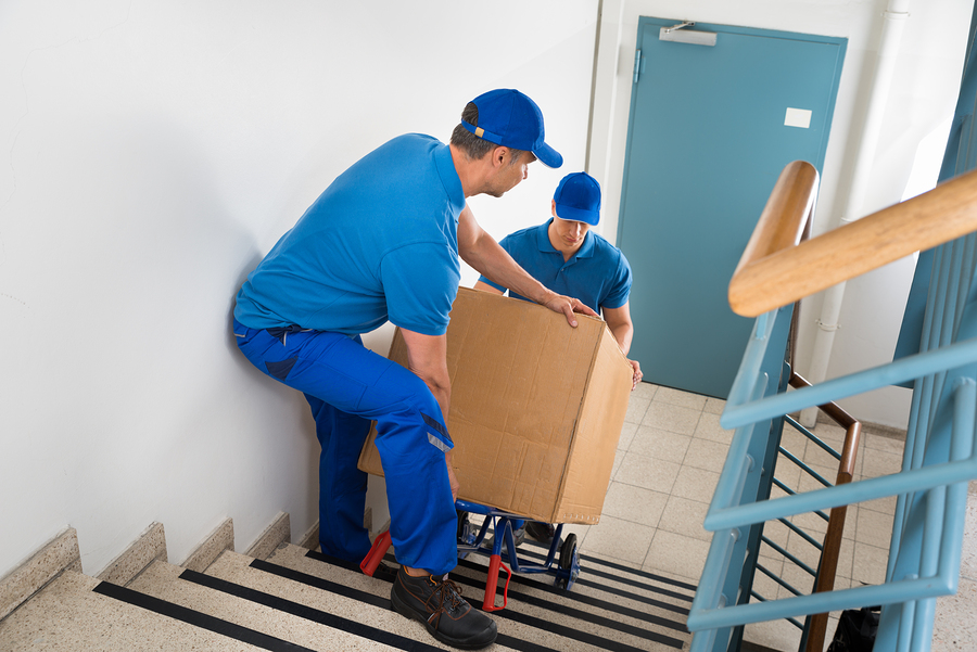 Two Male Movers Walking Downward With Box On Staircase