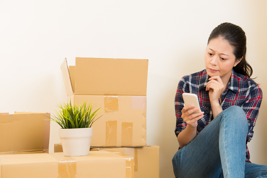 Young woman surrounded by moving boxes on smartphone trying to find a moving company