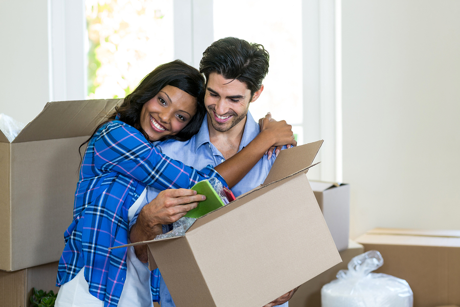 Young couple embracing while unpacking carton boxes after moving to a new apartment