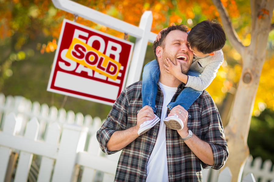 Dad and son laughing in front of home sold sign for moving in the fall