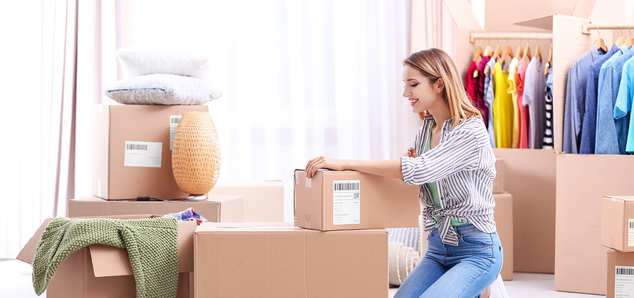 Young woman packing wardrobe boxes on moving day